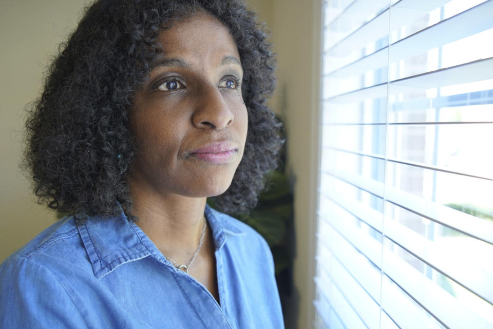 Tamika Dalton looks out of a window at her home in Durham, N.C., on Sept. 23, 2021. When COVID-19 kept visitors from going inside the Blumenthal Nursing and Rehabilitation Center in Greensboro, N.C, Dalton would often visit at her mother's window a couple times a day. Through the glass, Dalton didn't like what she saw: Fewer and fewer aides passed by, and her mother sometimes sat for hours in a soiled diaper. (AP Photo/Allen G. Breed)