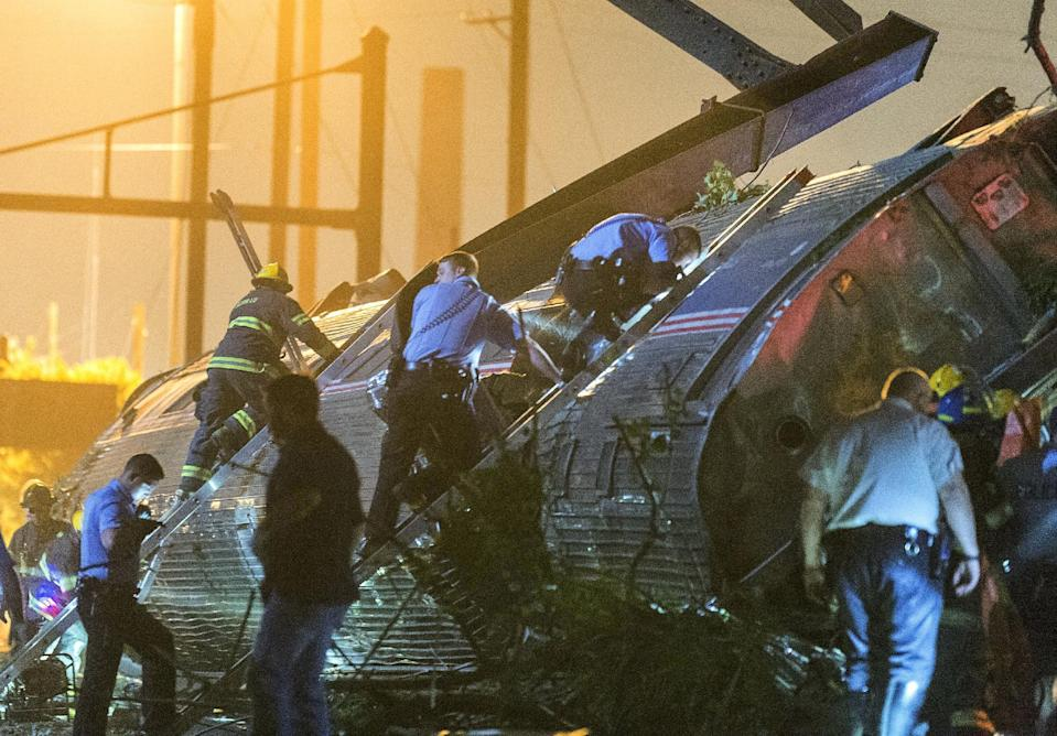 Rescue workers climb into the wreckage of a derailed Amtrak train to search for victims in Philadelphia, Pennsylvania May 12, 2015. The Amtrak passenger train with more than 200 passengers on board derailed in north Philadelphia on Tuesday night, killing at least five people and injuring more than 50 others, several of them critically, authorities said. Authorities said they had no idea what caused the train wreck, which left some demolished rail cars strewn upside down and on their sides in the city's Port Richmond neighborhood along the Delaware River. REUTERS/Bryan Woolston