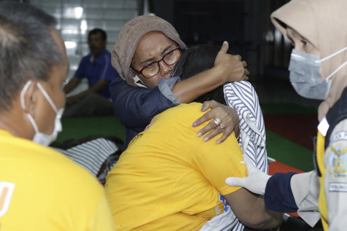 A relative embraces a survivor of the sinking ferry KMP Yunice at an evacuation point in Banyuwangi, East Java, Indonesia, early Wednesday, June 30, 2021. Rescuers searched into the night Tuesday for several missing people after the ferry sank in rough seas near Indonesia's resort island of Bali, killing a number of people, officials said. (AP Photo)