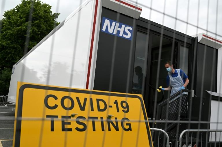A worker cleans down the doorway of a Covid-19 testing site in a car park in Penrith in Cumbria, northwest England, amid concerns over the Delta variant
