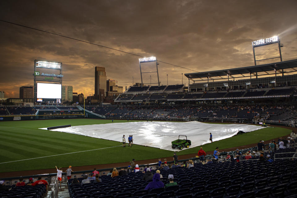 Grounds crew start to gather to remove the tarp to get the field ready for the game between Virginia and Texas in the College World Series Thursday, June 24, 2021, at TD Ameritrade Park in Omaha, Neb. (AP Photo/John Peterson)