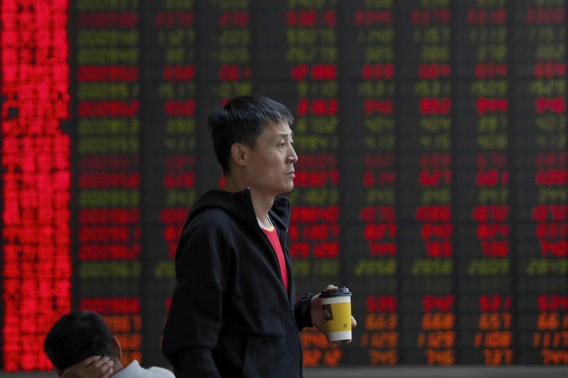 In this Thursday, Sept. 19, 2019, photo, a man holding a cup of coffee monitors the stock prices at a brokerage house in Beijing. Asian shares were mostly higher on Friday, Sept. 20, 2019 after a lackluster session on Wall Street, as investors shifted their focus to China-U.S. trade talks after a busy week of central bank news. (AP Photo/Andy Wong)
