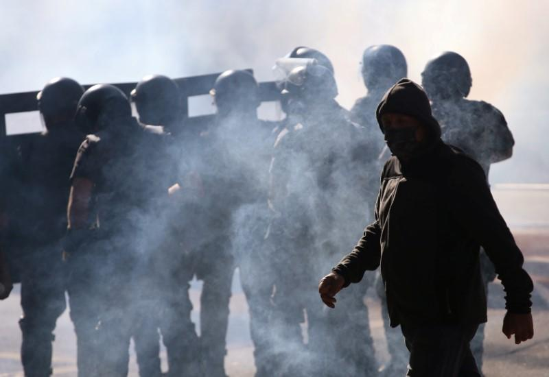 A man walks next to police officers among tear gas during a protest against Brazilian President Jair Bolsonaro in Sao Paulo