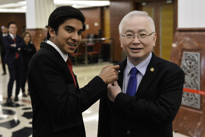 Minister of Youth and Sports Syed Saddiq Abdul Rahman pinned on a support for the Undi 18 Bill button on Ayer Hitam MP Datuk Seri Wee Ka Siong at Parliament on July 16, 2019. — Picture by Miera Zulyana