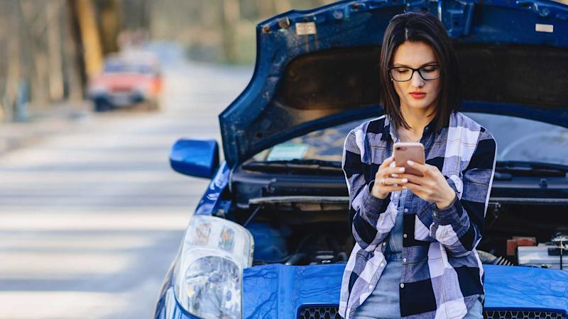 Woman with phone with broken down car on road