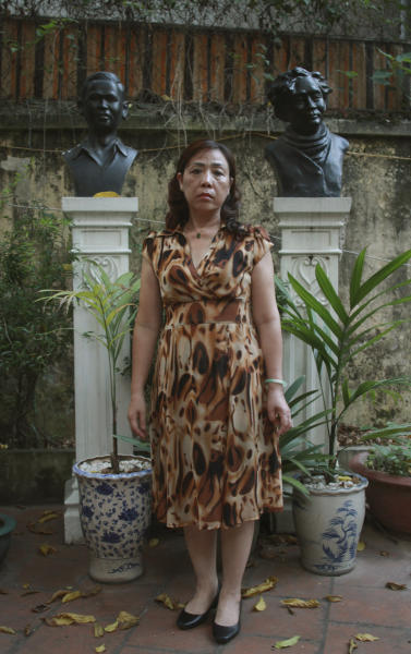 In this photo taken Monday, June 17, 2013, lawyer Nguyen Thi Duong Ha stands in the courtyard of her home in downtown Hanoi, Vietnam. Her husband Cu Huy Ha Vu is entering the fourth week of a prison hunger strike to protest alleged poor treatment. The statues seen in her background are of Vu's father, the poet Cu Huy Can, left, and his uncle Xuan Dieu, also a famous poet (right). Vu was jailed after suing the prime minister and calling for multiparty democracy. His strike comes amid an intensifying crackdown on dissident, and illustrates how the government's most outspoken critics speak out despite threats to their health and safety. (AP Photo/Mike Ives)
