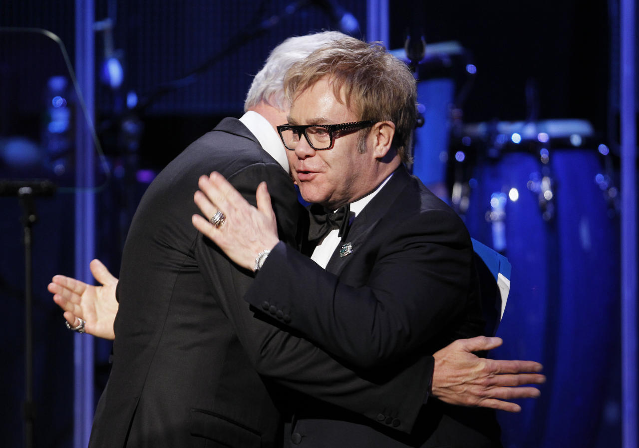 "Former U.S. President Bill Clinton (L) hugs singer Elton John after receiving an award during ""An Enduring Vision,"" a benefit dinner for the Elton John Aids Foundation in New York November 16, 2009. (REUTERS/Lucas Jackson)"