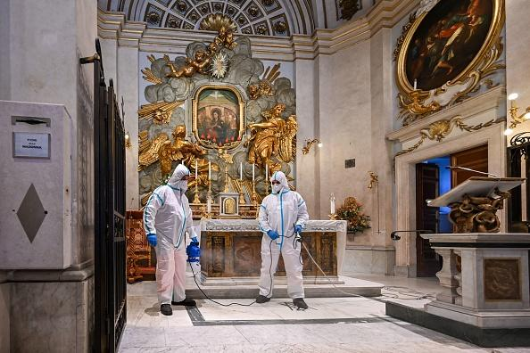 Employees of Rome's Municipal Environment Company (AMA), wearing protective overall and mask, sanitise the Santuario della Madonna del Divino Amore church in the southern Castel di Leva district of Rome.