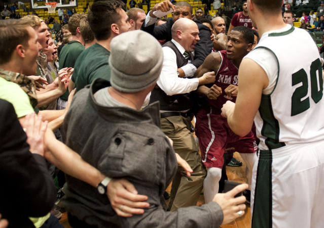In this Thursday, Feb. 27, 2014 photo, New Mexico State's DK Eldridge, at right center in red and white uniform, is controlled by security during a brawl involving players and fans who came onto the court when New Mexico State guard K.C. Ross-Miller hurled the ball at Utah Valley's Holton Hunsaker seconds after the Wolverines' 66-61 overtime victory against the Aggies in Orem, Utah. (AP Photo/The Daily Herald, Grant Hindsley)