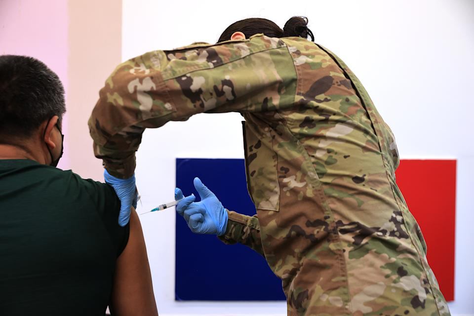A member of the Maryland National Guard administers a coronavirus vaccine