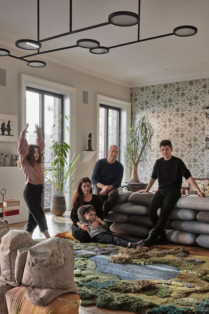 "<div class=""caption""> The family, lounging in the living room. </div>"
