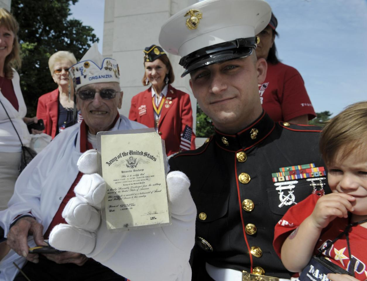 Marine Staff Sgt. Travis Hassell, center, and his son Issac show off Francis Slate's, left, Honorable Discharge Card from the U.S. Army Dec. 3, 1945, as they wait for President Barack Obama to deliver his Memorial Day address at Arlington National Cemetery in Arlington, Va., Monday, May 27, 2013. (AP Photo/Cliff Owen)