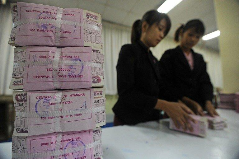 Myanmar employees handle bank notes at the central bank of Myanmar in Yangon on June 27, 2013