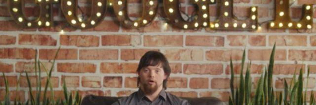 Person with Down syndrome sitting on a couch underneath a Google sign