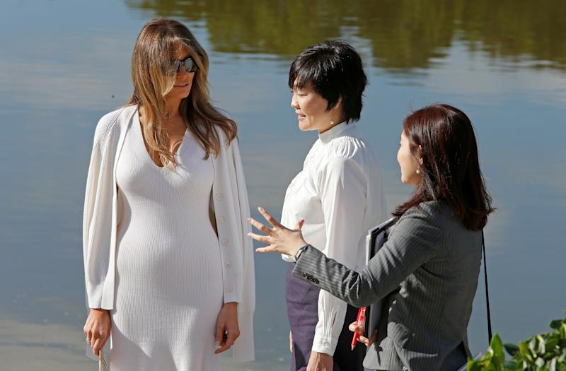 U.S. First Lady Melania Trump (L) and Akie Abe (C), wife of Japanese Prime Minister Shinzo Abe, listen to an interpreter as they tour Morikami Museum and Japanese Gardens in Delray Beach, Florida, U.S., February 11, 2017.  REUTERS/Joe Skipper