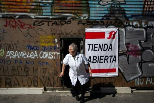 """Some shops in Valparaiso have """"Store Open"""" signs, but they are still boarded up or leave their security screens down, forcing customers to enter through small openings"""