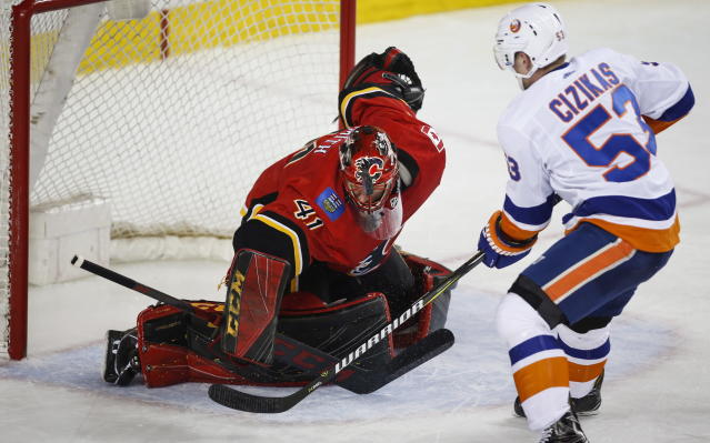 New York Islanders' Casey Cizikas, right, has his shot deflected by Calgary Flames goalie Mike Smith during second-period NHL hockey game action in Calgary, Alberta, Sunday, March 11, 2018. (Jeff McIntosh/The Canadian Press via AP)