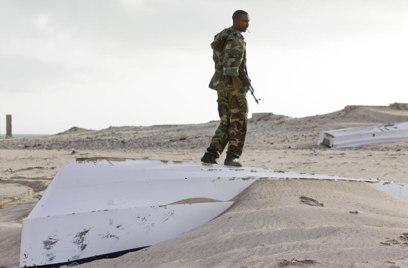 In this photo taken Sunday, Sept. 23, 2012, a Somali government soldier stands over one of the overturned pirate skiffs that litter the dunes on the shoreline near the once-bustling pirate den of Hobyo, Somalia. The empty whisky bottles and overturned, sand-filled skiffs that litter this shoreline are signs that the heyday of Somali piracy may be over - most of the prostitutes are gone, the luxury cars repossessed, and pirates talk more about catching lobsters than seizing cargo ships. (AP Photo/Farah Abdi Warsameh)