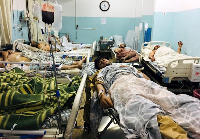Wounded Afghans lie on a bed at a hospital after an attack on the airport in Kabul, Afghanistan, on Aug. 26.