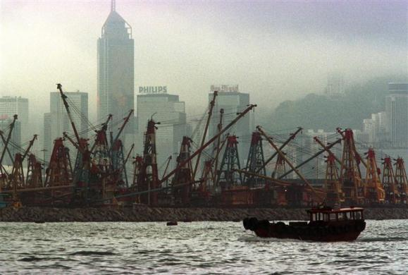 A lone sampan floats by barges inside a typhoon shelter in Victoria harbor June 22, 1997 as a low mist covers the skyscrapers of Hong Kong.