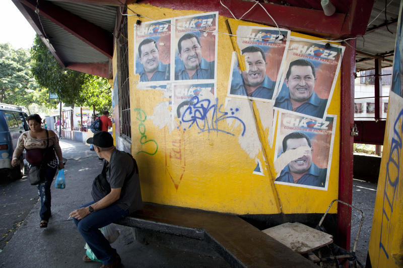 A man sits next to posters with images of Venezuela President Hugo Chavez in Caracas, Venezuela, Thursday, Jan. 3, 2013. The ailing president's health crisis has raised contentious questions ahead of the swearing-in set for Jan. 10, including whether the inauguration could legally be postponed. Officials have raised the possibility that Chavez might not be well enough to take the oath of office, without saying what will happen if he can't. The constitution says that if a president or president-elect dies or is declared unable to continue in office, presidential powers should be held temporarily by the president of the National Assembly and that a new presidential vote should be held within 30 days. (AP Photo/Ariana Cubillos)
