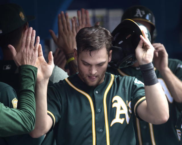 Oakland Athletics' Chad Pinder celebrates in the dugout after scoring in the sixth inning of a baseball game against the Toronto Blue Jays in Toronto, Sunday May 20, 2018. (Fred Thornhill/The Canadian Press via AP)