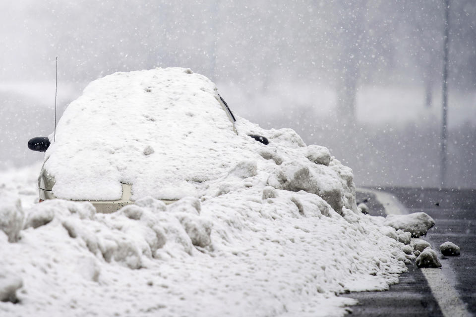 An abandoned car is covered in snow on the shoulder of Briley Parkway in Nashville, Tennessee, February 18. Source: The Tennessean via AP