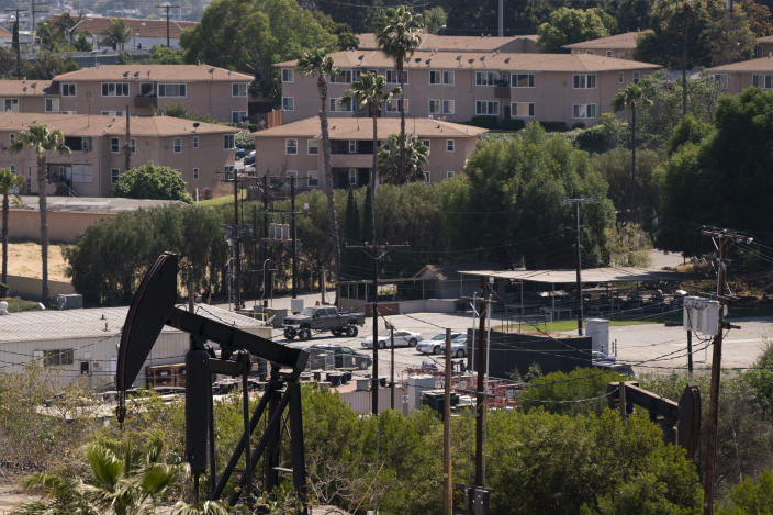 FILE - In this May 18, 2021, file photo, apartment buildings rise behind pump jacks operating at the Inglewood Oil Field in Los Angeles. California state oil regulators missed a spring deadline for new regulations designed to protect health and safety near oil and gas drillings sites. Environmental advocates have been pressuring Gov. Gavin Newsom's administration to adopt mandatory distances between wells and sites like schools and homes. (AP Photo/Jae C. Hong, File)