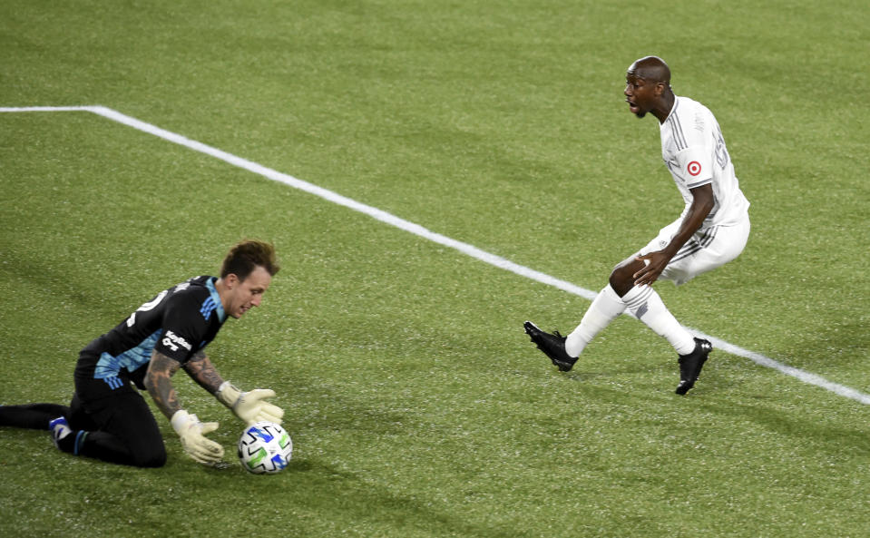Portland Timbers goalkeeper Steve Clark, left, stops the shot of Los Angeles FC forward Bradley Wright-Phillips, right, during the first half of an MLS soccer match in Portland, Ore., Sunday, Oct. 18, 2020. (AP Photo/Steve Dykes)