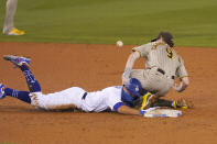 San Diego Padres shortstop Jake Cronenworth, right, loses the ball and is unable to tag out Los Angeles Dodgers' Chris Taylor as he dives back to second during the seventh inning of a baseball game Monday, Aug. 10, 2020, in Los Angeles. Padres catcher Austin Hedges was charged with an error the throw and Taylor advanced to third on the play. (AP Photo/Mark J. Terrill)