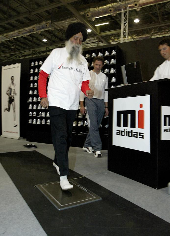 LONDON, ENGLAND - APRIL 15:  Fauja Singh, 93 and the oldest competing runner in the London Marathon, designs his own shoe at the Adidas stand at the Marathon Exhibition being held at the Excel Centre on April 15, 2004 in London. (Photo by John Gichigi/Getty Images for adidas)