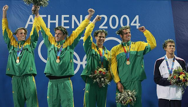 ATHENS - AUGUST 15: Michael Phelps of USA looks on as the relay team of South Africa stand on the podium after breaking the world record and winning gold in the men's swimming 4 x 100 metre freestyle relay final on August 15, 2004 during the Athens 2004 Summer Olympic Games at the Main Pool of the Olympic Sports Complex Aquatic Centre in Athens, Greece. (Photo by Daniel Berehulak/Getty Images for FINA)