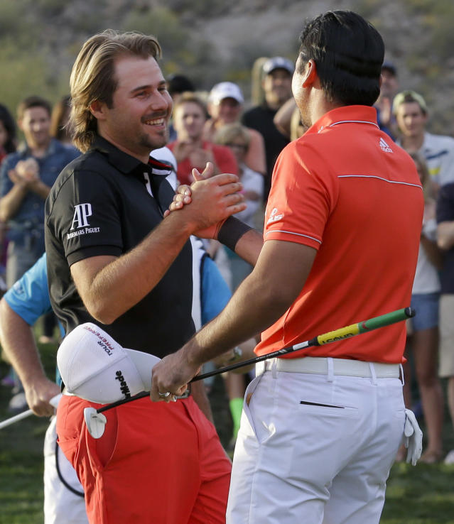 Jason Day, of Australia, right, shakes hands on the 23rd hole after winning his championship match against Victor Dubuisson, of France, during the Match Play Championship golf tournament, Sunday, Feb. 23, 2014, in Marana, Ariz. (AP Photo/Ted S. Warren)