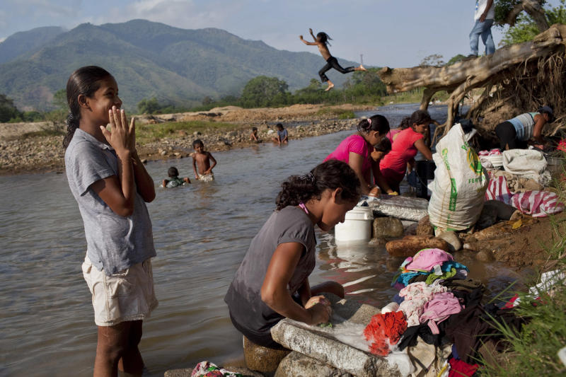 In this May 6, 2012 photo, women wash clothes on the river banks near La Confianza, Honduras, a city developed from land seized by small-scale farmers from one of Honduras' richest men. The collection of tin-and-wood shacks boasts a health center, a school, a meeting hall, and a store. The land seizure has spawned a violent land conflict between the farmers and owner, billionaire Miguel Facusse, that has killed at least 63 people, mostly peasants, in the last three years in the Bajo Aguan Valley. (AP Photo/Rodrigo Abd)