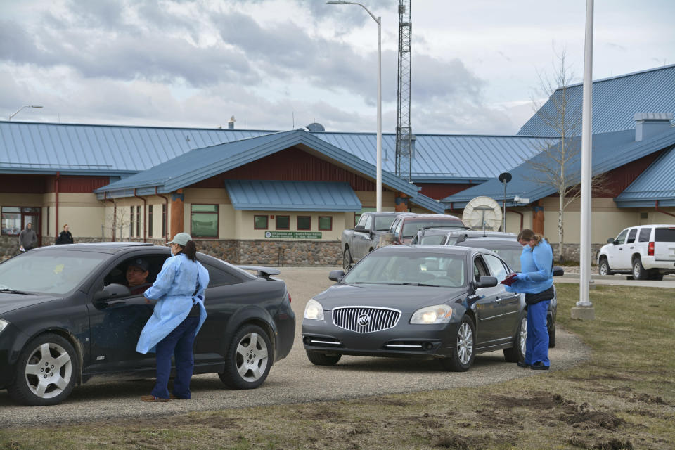 In this Thursday, April 29, 2021, photo, nurses interview patients through their car windows after providing them with COVID-19 vaccines at the Piegan-Carway border crossing after they drove from Canada to Montana to receive excess doses from the Blackfeet tribe, near Babb, Mont. (AP Photo/Iris Samuels)