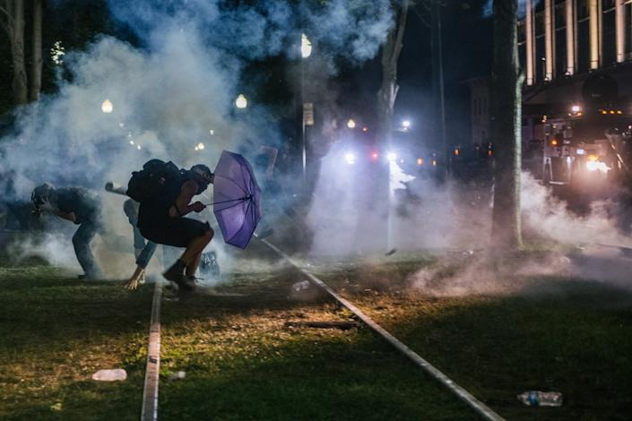 Demonstrators retreat from tear gas in front of the Kenosha County Courthouse.