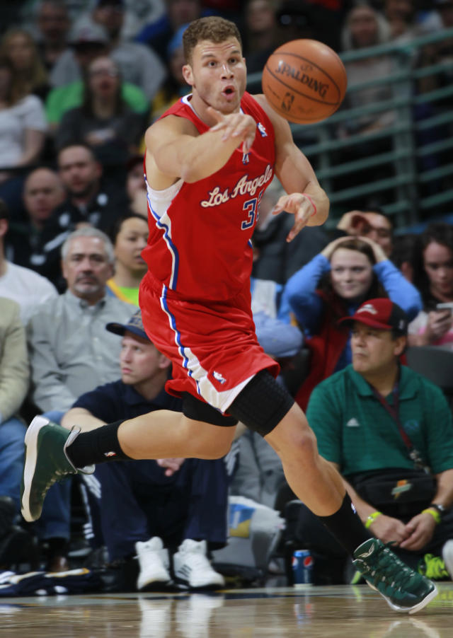 Los Angeles Clippers forward Blake Griffin reaches out to pull in a loose ball against the Denver Nuggets in the first quarter of an NBA basketball game in Denver on Monday, March 17, 2014. (AP Photo/David Zalubowski)