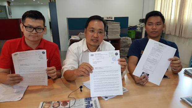 Bandar Kuching MP Chong Chieng Jen (centre) with a car owner Lim Tze Wei (right) showing a traffic summons issued to Lim at a press conference, April 11, 2017. ― Picture by Sulok Tawie