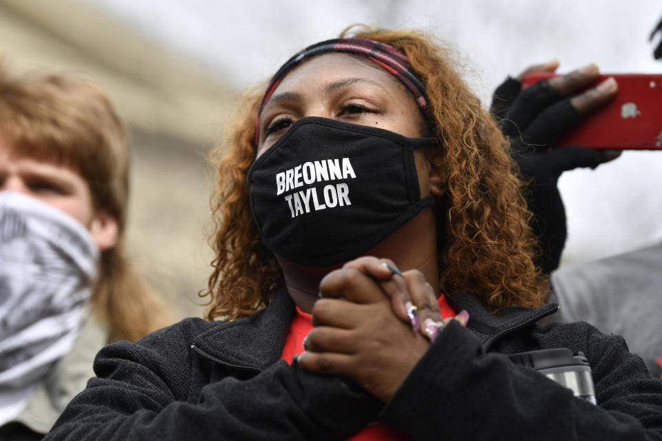 A protester listens to the speakers during a rally on the one year anniversary of the death of Breonna Taylor at Jefferson Square Park in Louisville, Ky., Saturday, March 13, 2021. (AP Photo/Timothy D. Easley)
