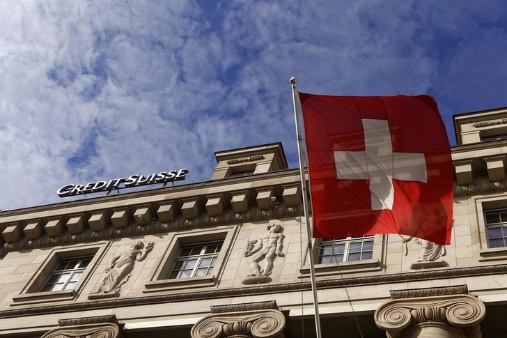 A national flag of Switzerland flies in front of a branch office of Swiss bank Credit Suisse in Luzern