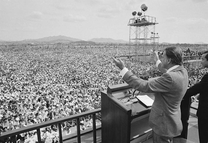 American evangelist Billy Graham gestures as he preaches to over half a million South Koreans at a plaza on Yoido islet in Seoul, June 3, 1973, in the final day of a five-day crusade there.