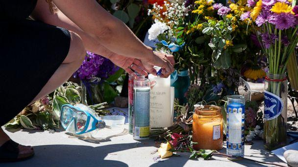 A woman relights a candle placed at a memorial for the victims of the Conception dive boat on the Santa Barbara Harbor on Sunday, Sept. 8, 2019 in Santa Barbara, Calif. Authorities served search warrants Sunday at the Southern California company that (The Associated Press)