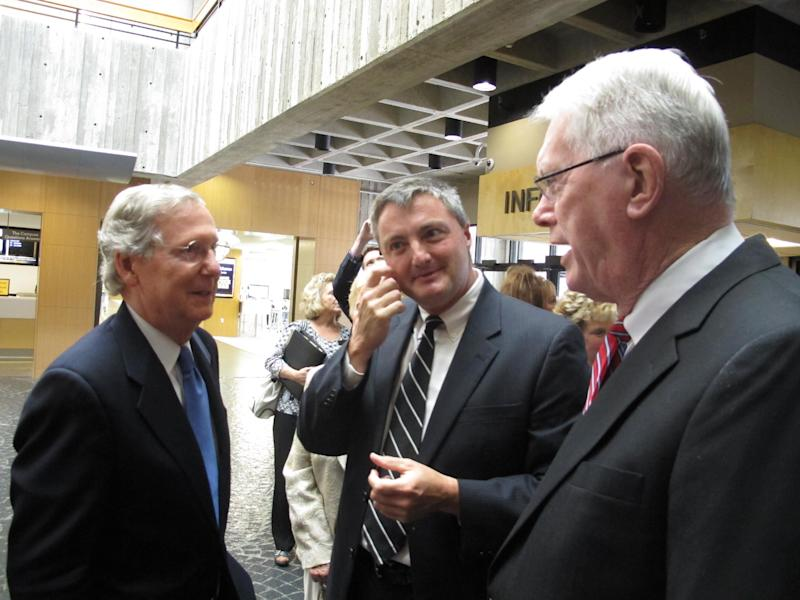 Senate GOP Leader Mitch McConnell, left, talks with former U.S. Sen. Jim Bunning, right, and his son, U.S. District Judge David Bunning, at Northern Kentucky University in Highland Heights, Ky., on Friday, Sept. 6, 2013. McConnell praised Bunning in a lecture he delivered at the university. (AP Photo/Roger Alford)