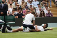 Australia's Nick Kyrgios receives treatment on the court during the men's singles third round match against Canada's Felix Auger-Aliassime on day six of the Wimbledon Tennis Championships in London, Saturday July 3, 2021. (AP Photo/Alberto Pezzali)