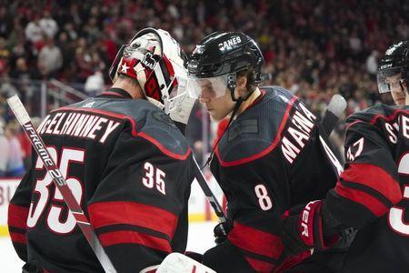 Jan 11, 2019; Raleigh, NC, USA; Carolina Hurricanes goaltender Curtis McElhinney (35) celebrates with right wing Saku Maenalanen (8) after their win against the Buffalo Sabres at PNC Arena. The Carolina Hurricanes defeated the Buffalo Sabres 4-3. Mandatory Credit: James Guillory-USA TODAY Sports