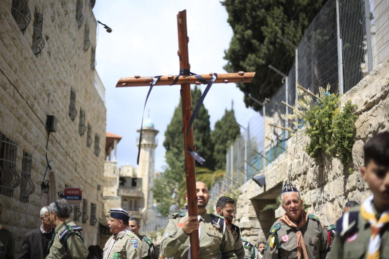 Christians from the boys scouts movement, one carrying a cross, walk along the Via Dolorosa towards the Church of the Holy Sepulchre, traditionally believed by many to be the site of the crucifixion of Jesus Christ, during the Good Friday procession in Jerusalem's old city, Friday, April 19, 2019. (AP Photo/Ariel Schalit)