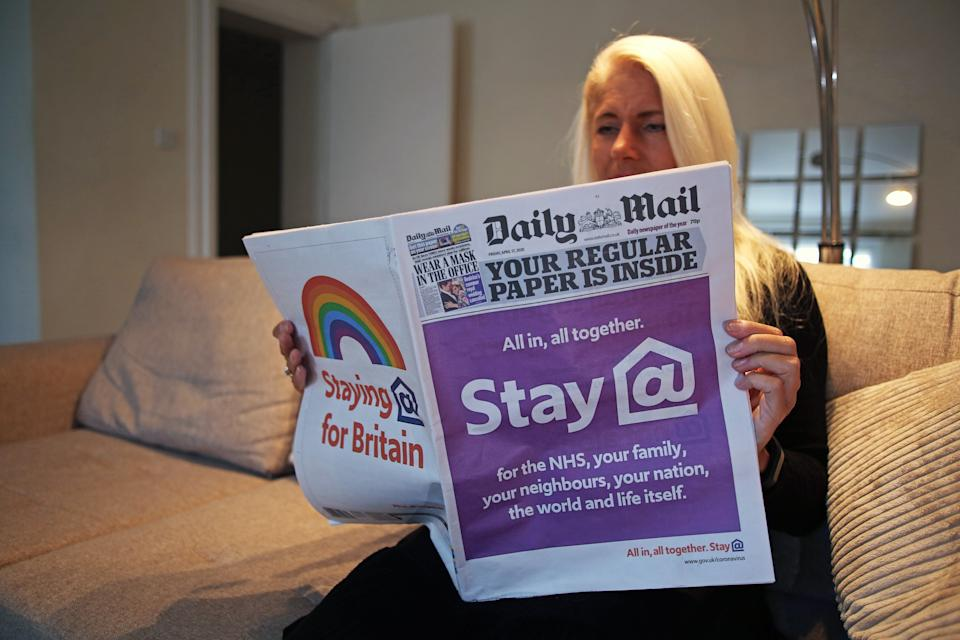 A woman reads a special edition of the Daily Mail newspaper, which displays a NHS coronavirus message on the front pages saying 'All in, all in together. Stay at home' and 'staying home for Britain' as the UK continues in lockdown to curb the spread of coronavirus.