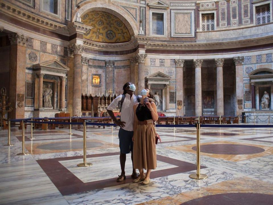Couple enjoying the empty Pantheon in Rome, wearing protective face masks during COVID-19 pandemic - stock photo