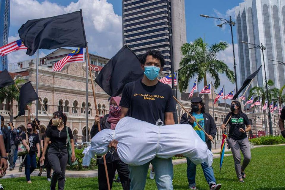 Protesters wearing personal protective equipment (PPE) hold black flags and effigies of corpses during the Black Flag protest demanding the resignation of prime minister Tan Sri Muhyiddin Yassin. — Picture by Shafwan Zaidon