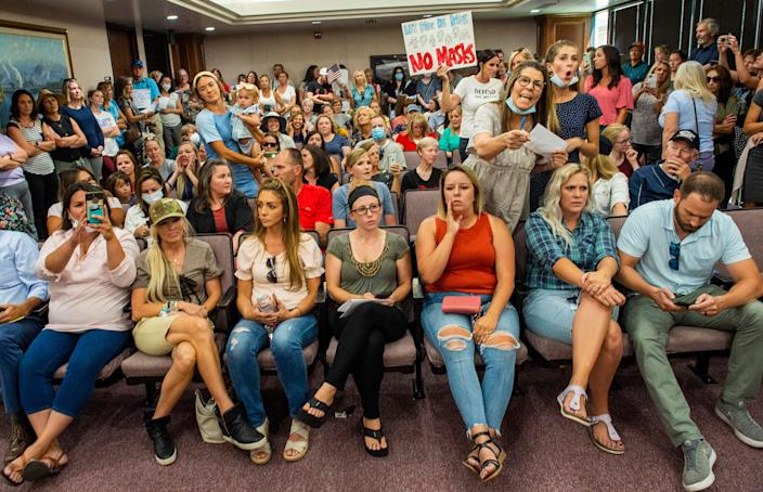 Angry residents react when the Utah County Commission meeting was adjourned before it even started, Wednesday, July 15, 2020, in Provo, Utah. The group protesting against face masks being required in schools removed the social distancing tape on the chairs and filled the Utah County Commission room to over flowing, prompting Commissioner Tanner Ainge to call for a vote to adjourn the meeting.